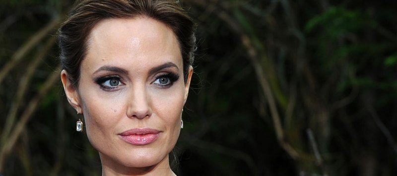 Angelina Jolie stands perfectly still, unshowered, covered in bees for World Bee Day